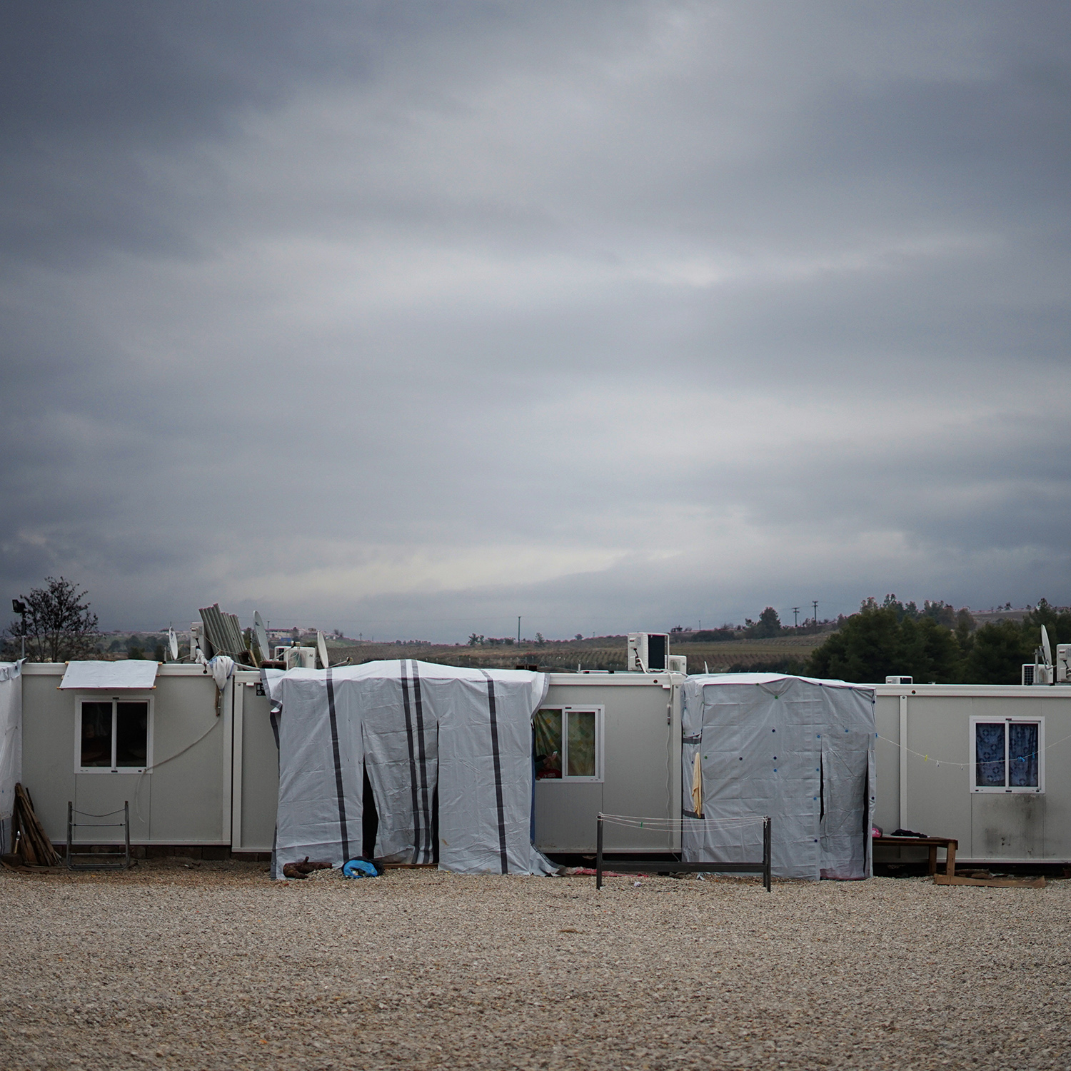 photograph of small, temporary housing units in a desolate area.