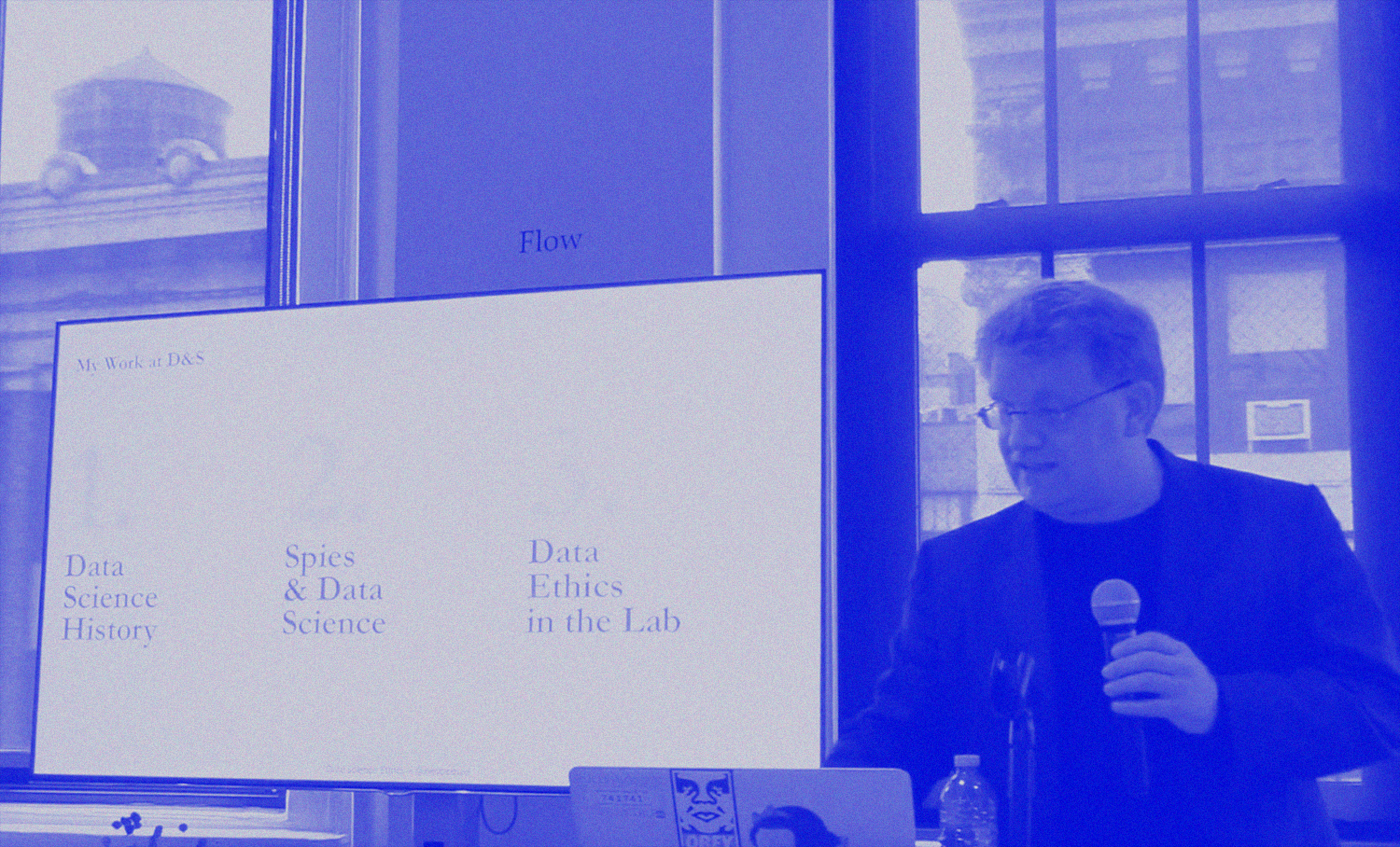 photo of man with short hair and glassed presenting next to a monitor that lists examples of his work at data & society.