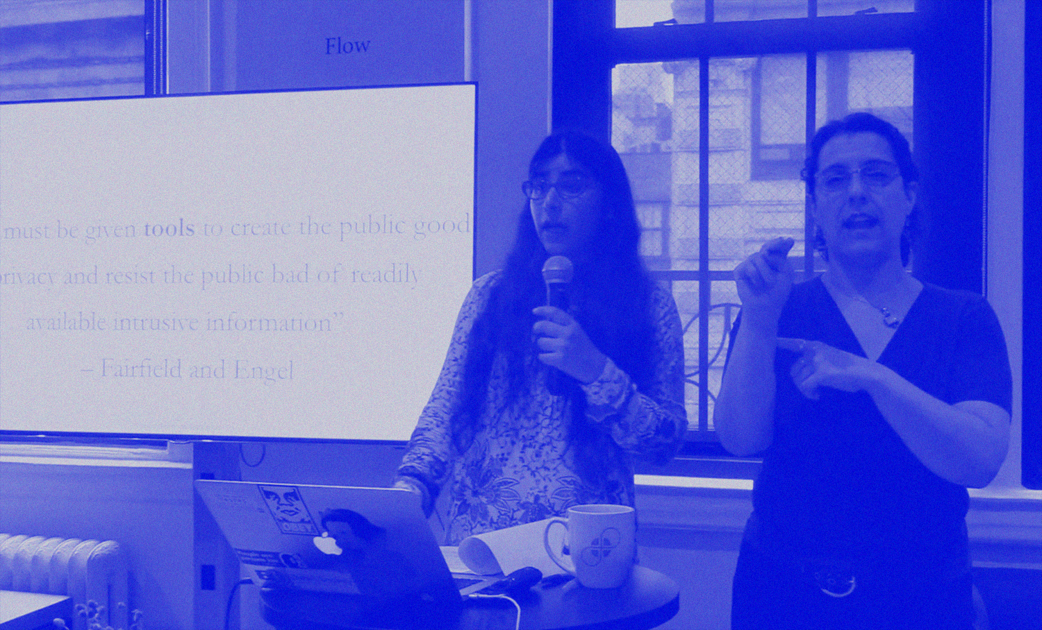 photo of person with long hair speaking into microphone and a sign-language interpreter signing the presentation for the audience.