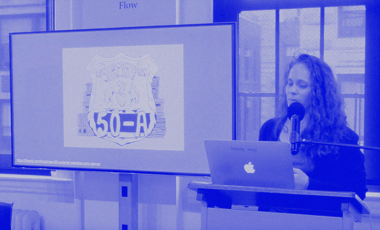 photo of person with long hair speaking into a microphone next to a screen with a large illustration of an NYPD badge with the word
