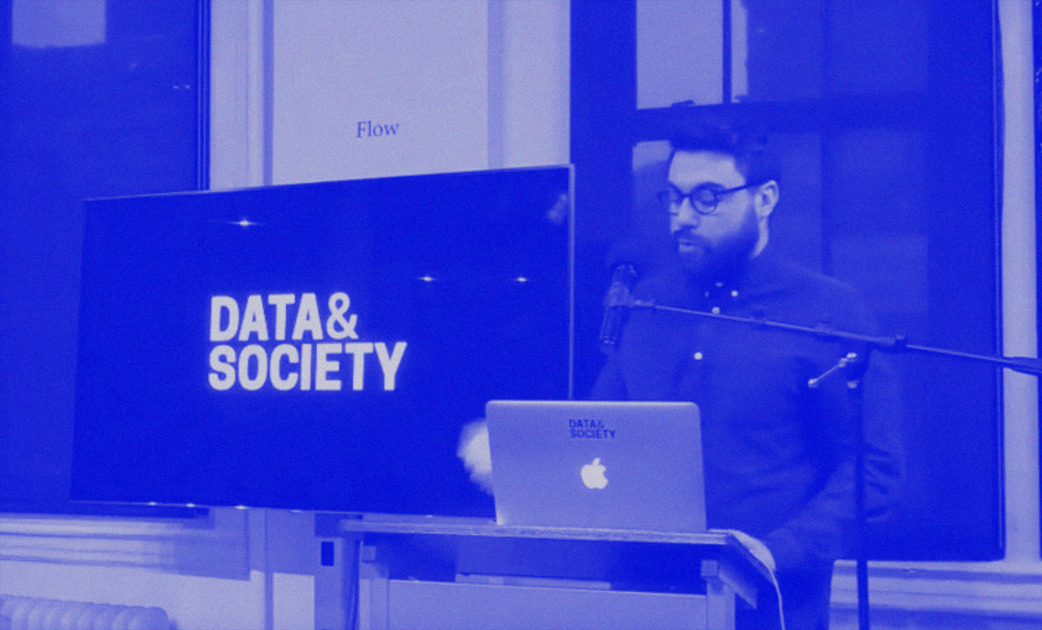 photo of person with facial hair and glasses presenting in front of screen that says