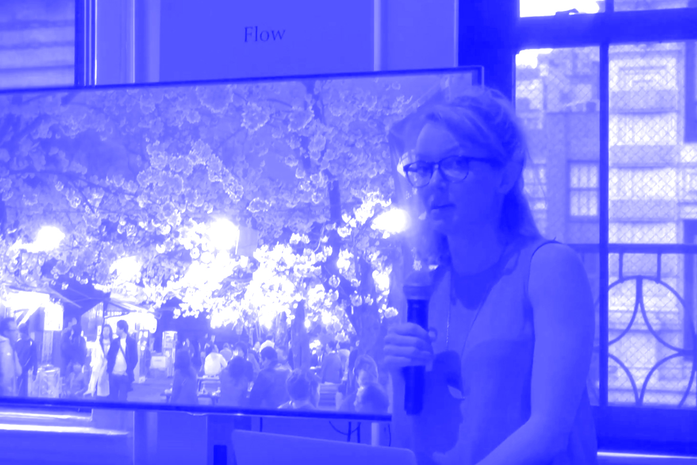 photo of person holding microphone presenting in front of large monitor with an image of blooming trees.